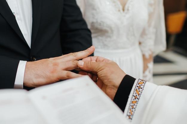 Cerimônia de casamento. padre coloca aliança na mão do noivo