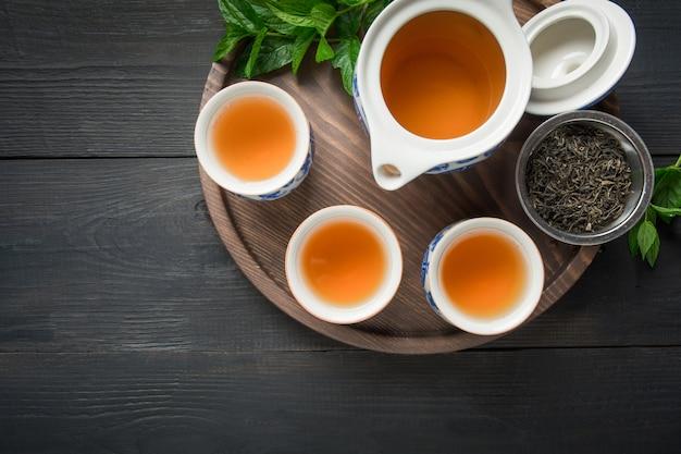 Cerimônia do chá. xícaras de chá com melissa e chaleira no escuro