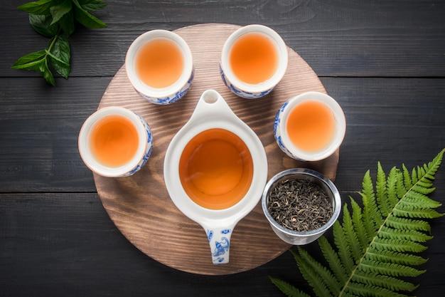 Cerimônia do chá. xícaras de chá verde com hortelã e chaleira no escuro. conceito de chá chinês. vista de cima.