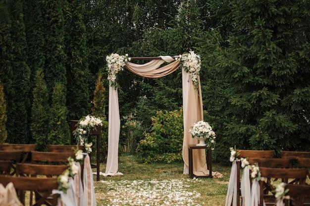 Cerimônia externa muito bonita. casamento clássico na floresta. o arco é de madeira. flores brancas. cadeiras marrons. rito. noiva e noivo. decoração. florística. ao ar livre. caminho das pétalas de rosas.
