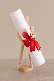 Certificado de diploma de educação realizado por boneco de madeira