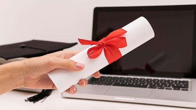 Certificado de diploma de graduação e laptop