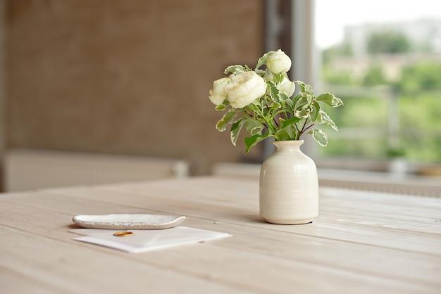 Certificado de presente de aniversário de convite de casamento para um spa ou cartão de carta decorado com cuidado em uma mesa de madeira branca em frente a uma janela panorâmica