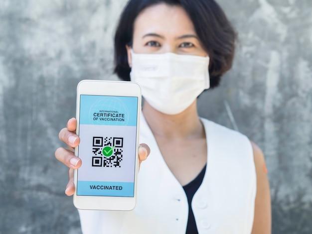 Certificado internacional de vacinação, passaporte digital inteligente com código qr na tela do smartphone. mulher asiática vacinada com curativo mostrando passaporte sanitário ou certificado de vacinação.