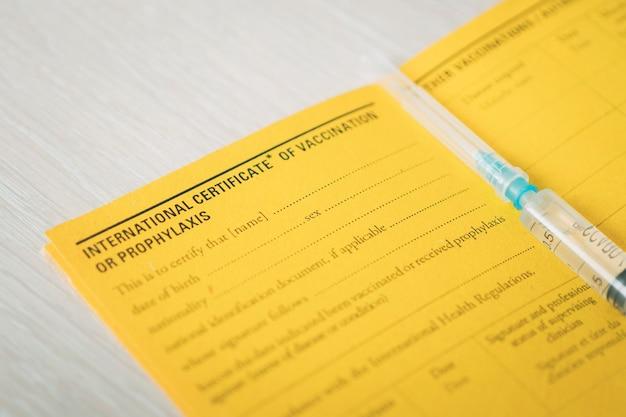 Certificado internacional de vacinação um documento para registro das vacinas realizadas. o documento é amarelo. passaporte de cidadão estrangeiro e seringa em cima da mesa. conceito de viagem segura.