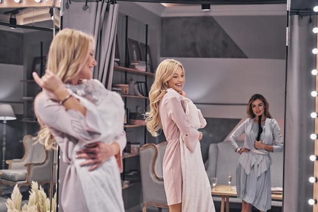 Certificando-se de que está perfeito. mulheres jovens e atraentes experimentando um vestido de noiva enquanto passam um tempo na loja de noivas com a namorada