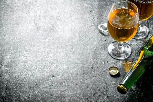 Cerveja a copo e garrafa. sobre fundo preto rústico