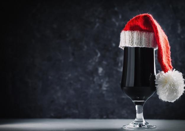 Cerveja artesanal de natal imperial stout ou porteiro em copyspace de chapéu de papai noel