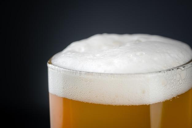Cerveja artesanal de vidro fresca e gelada com espuma branca no topo.