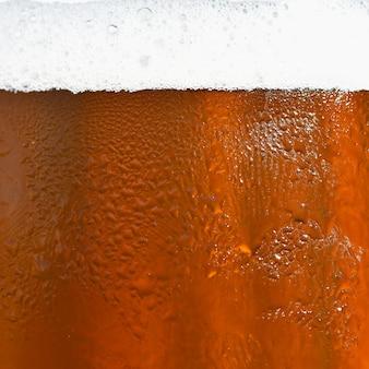 Cerveja. belo detalhe de copo de cerveja batido com espuma. fundo colorido abstrato.