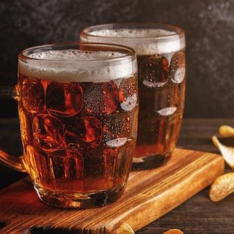 Cerveja cerveja gelada em copo com batatas fritas em fundo escuro