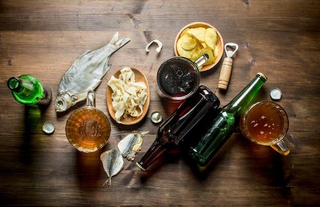 Cerveja com batatas fritas e rodelas de lula na tigela e peixe seco na mesa rústica