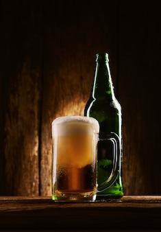 Cerveja com garrafa na caneca na mesa de madeira