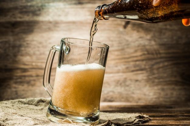 Cerveja da garrafa derramada em pé de caneca na lona