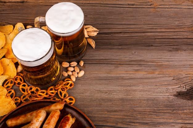 Cerveja de close-up com lanches na mesa de madeira