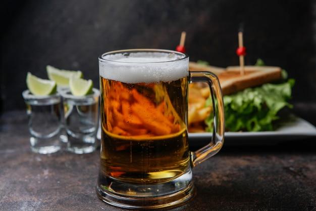 Cerveja de vista lateral com um prato de sanduíche e batatas fritas e tequila em um copo servido com limão e sal