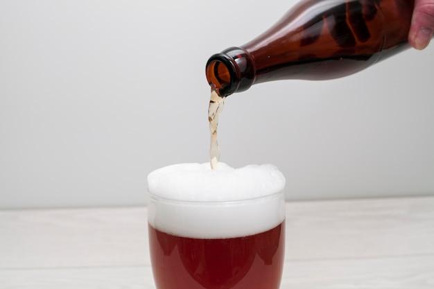 Cerveja derramada da garrafa de vidro com espuma