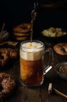 Cerveja, derramando em vidro com pretzels, salsicha e salgadinhos na mesa de madeira rústica