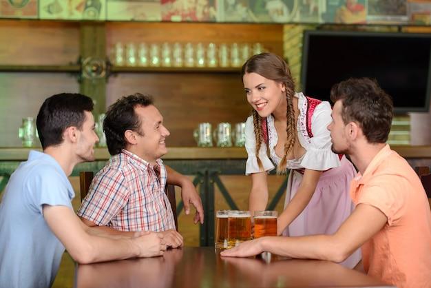 Cerveja do serviço da empregada de mesa quando três homens que sentam-se na tabela.