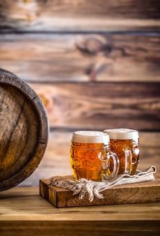 Cerveja. duas cervejas geladas. chope. cerveja de pressão. cerveja dourada. golden ale. duas cervejas douradas com espuma por cima. chope de cerveja gelada em potes de vidro em um hotel-pub ou restaurante caseiro. ainda vida.