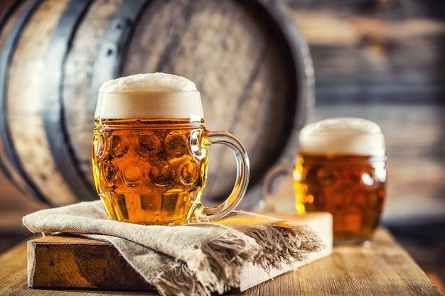 Cerveja. duas cervejas geladas. chope. cerveja de pressão. cerveja dourada. golden ale. duas cervejas douradas com espuma por cima. chope de cerveja gelada em potes de vidro em um hotel-pub ou restaurante caseiro. ainda vida. Foto Premium