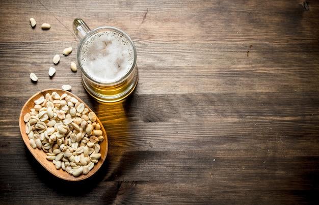 Cerveja e amendoim na tigela. em fundo de madeira