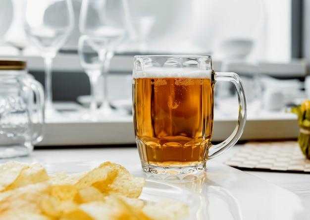 Cerveja e batatas fritas na grande mesa branca