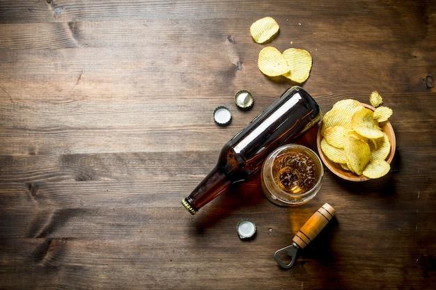 Cerveja e batatas fritas na tigela. em fundo de madeira
