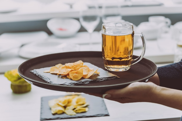 Cerveja e batatas fritas no prato grande.