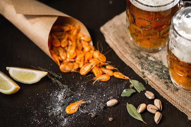 Cerveja e camarão grelhado na mesa de madeira