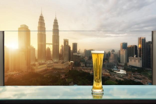 Cerveja e cerveja da espuma na tabela na barra do telhado com kuala lumpur, malásia.