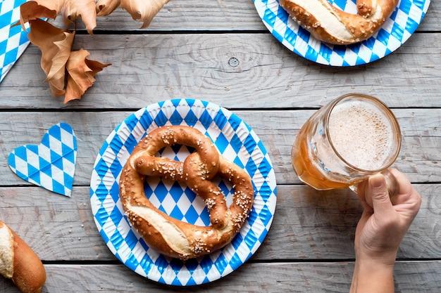 Cerveja e comida tradicional da oktoberfest. mão segurando a caneca de cerveja, pretzels em pratos de papel