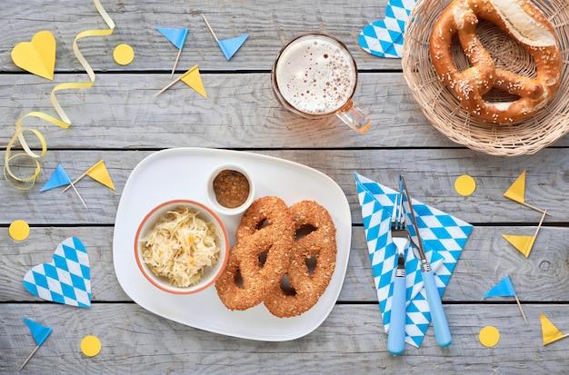 Cerveja e comida tradicional da oktoberfest. pretzels leberwurst com chucrute, pretzels de pão e decorações