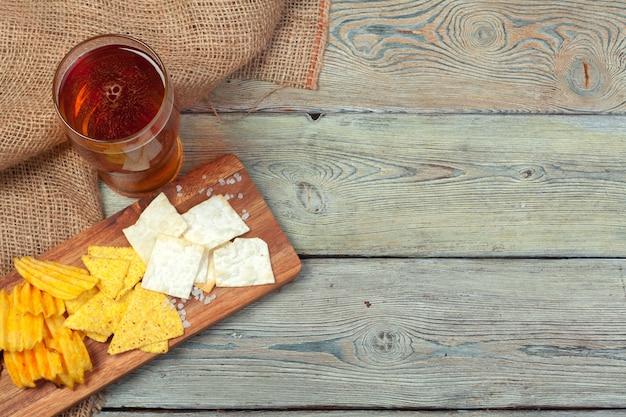 Cerveja e lanches na mesa de madeira.