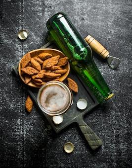 Cerveja e migalhas em uma placa de corte preta.