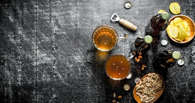 Cerveja e salgadinhos nas tigelas. em fundo rústico