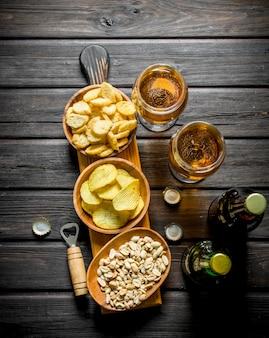 Cerveja e vários tipos de petiscos nas tigelas da tábua de corte.