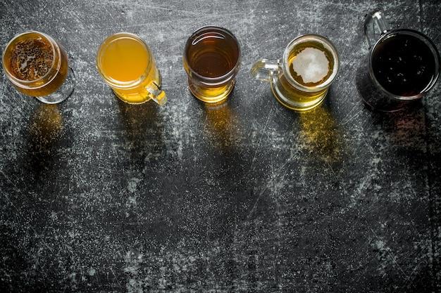 Cerveja em copos diferentes em mesa rústica