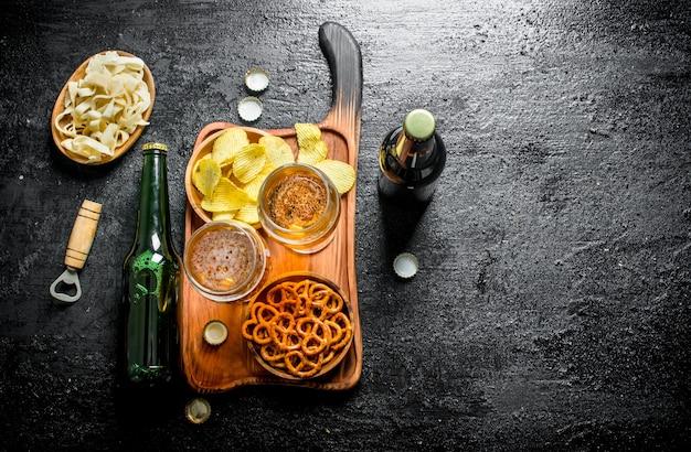 Cerveja em copos e garrafa e petiscos em tigelas. sobre fundo preto rústico
