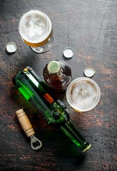 Cerveja em copos e garrafas com abridor e tampas. em superfície rústica