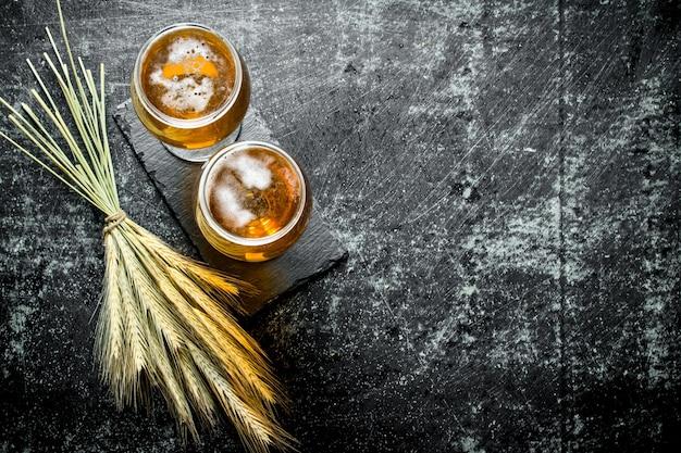 Cerveja em copos em um estande e um monte de espigas. na superfície rústica preta