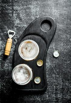 Cerveja em copos em uma placa de corte preta com abridor e tampas. na superfície rústica preta