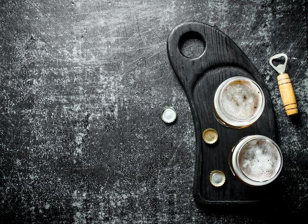 Cerveja em copos em uma tábua preta com abridor e tampas em mesa rústica preta