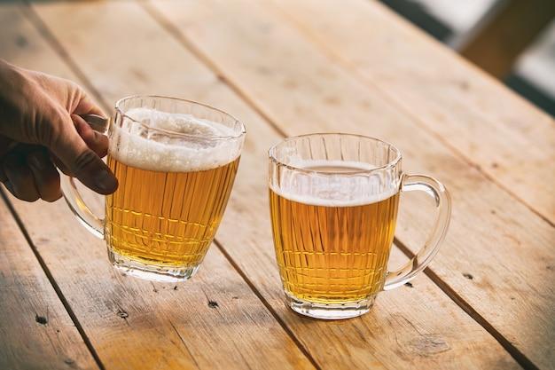 Cerveja em copos grandes e vidro claro dourado com espuma e close-up de mão