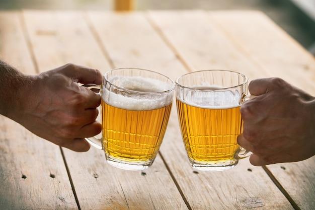 Cerveja em copos grandes e vidro claro dourado com espuma e mãos de amigos close-up