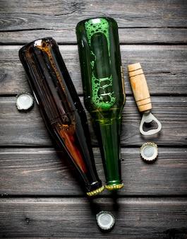 Cerveja em garrafas de vidro e abridor. na mesa de madeira