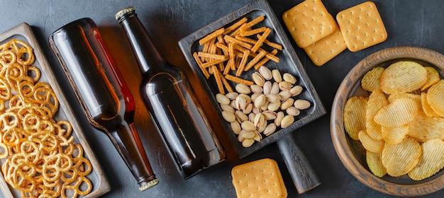 Cerveja em garrafas de vidro e salgadinhos para cerveja. fundo cinza de concreto. o conceito de festa para amigos.