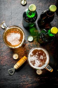 Cerveja em garrafas e copos. na mesa rústica