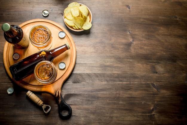 Cerveja em garrafas e copos na tábua e batatas fritas na tigela. em fundo de madeira