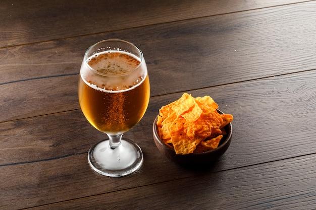 Cerveja em um copo de vidro com chips de alto ângulo vista sobre uma mesa de madeira